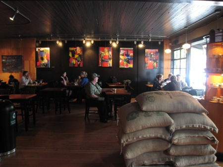 The café was very dark on the first floor. Dark wood paneling lined the floors and ceilings, and vibrant, colorful paintings stood out along the painted black walls