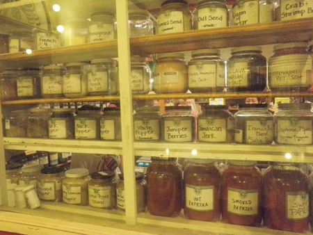 Jars of ground spices line the shelves of a MarketSpice window.